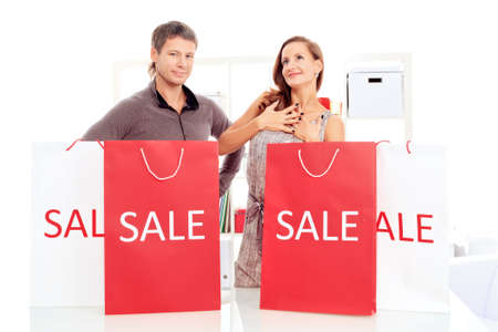 Seasonal sale: happy couple holding shopping bags inside of a store. Stock Photo - 15963532
