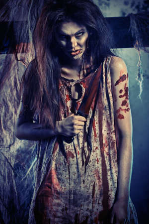 woman knife: Bloodthirsty zombi with a knife standing at the night cemetery in the mist and moonlight.
