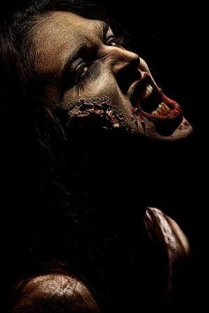 Gros plan d'un zombi sanguinaire sur fond noir.