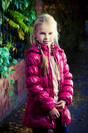 Portrait of a cute little girl standing at the autumn park. photo