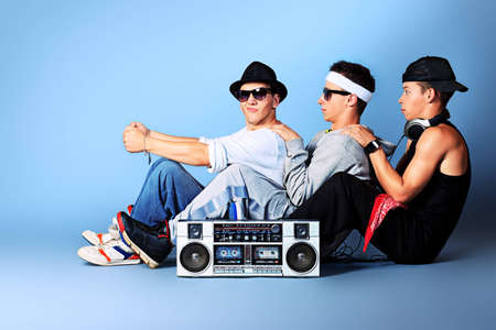 Group of trendy teenagers posing with boombox at studio. photo
