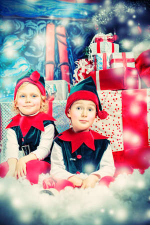 christmas costume: Two cute children in christmas elf costumes posing over christmas background.