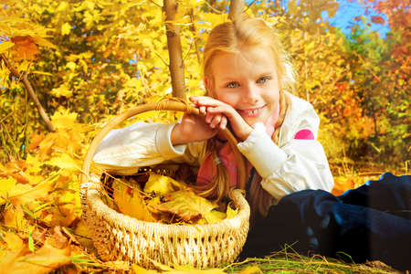 Portrait of a cute girl with a basket full of leaves posing at the autumn park. photo