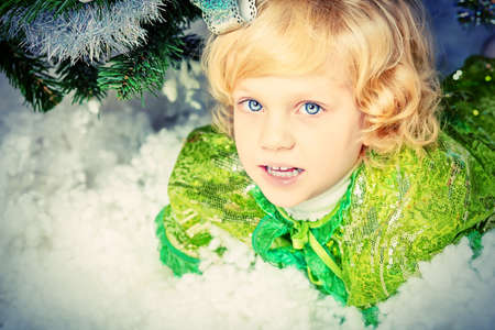 Happy little girl in Christmas dress lying in snow. Stock Photo - 15963690