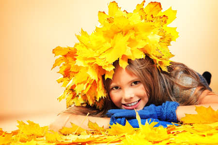 Portrait of a smiling girl in autumn clothes and a hat of maple leaves. Stock Photo - 16001080