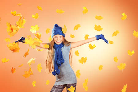 Joyful cute girl in autumn clothes throwing maple leaves. Stock Photo - 16001032
