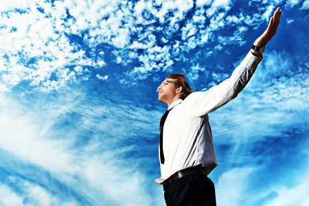 purposeful: Successful business man standing over blue sky and purposefully looking away.