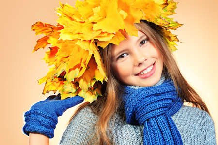 Portrait of a smiling girl in autumn clothes and a hat of maple leaves. Stock Photo - 16001124