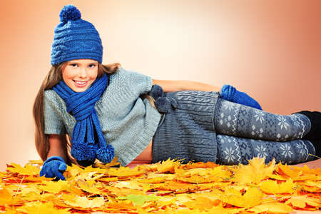 Portrait of a cute girl in autumn clothes lying on the maple leaves. Stock Photo - 16001106
