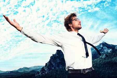 persona feliz: Exitoso hombre de negocios de pie en la cima de la montaña y mirando a otro lado a propósito.