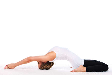 Slender young woman doing yoga exercise. Isolated over white background.  photo