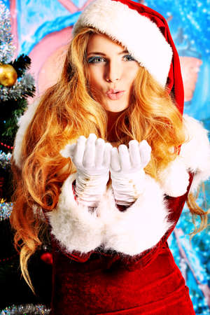Beautiful young woman in Santa Claus clothes over Christmas background. photo
