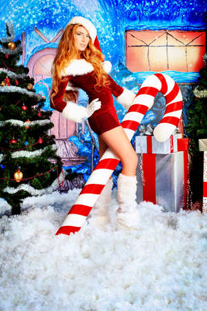 Beautiful young woman in Santa Claus clothes over Christmas background  photo