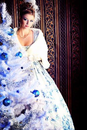 maquillaje fantasia: Retrato de la mujer elegante posando con �rbol de Navidad sobre fondo vintage.