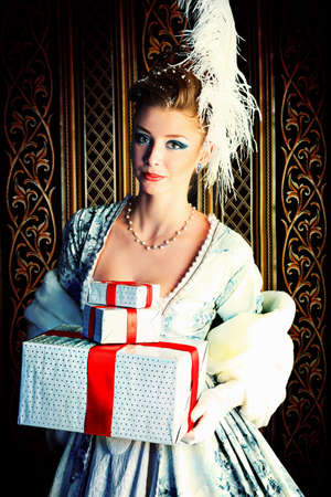 Portrait of the elegant woman posing with Christmas present over vintage background.  photo