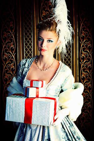 vestido medieval: Retrato de la mujer elegante posando con regalo de Navidad sobre fondo vintage. Foto de archivo