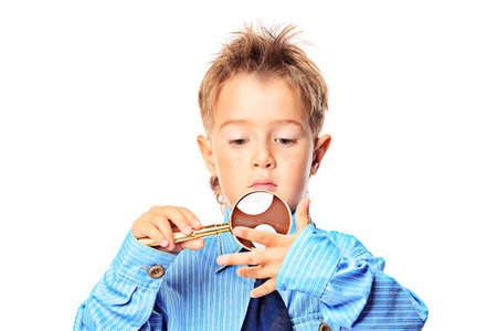 Curious little boy in spectacles is looking through a magnifying glass. Isolated over white background. Stock Photo - 16058213