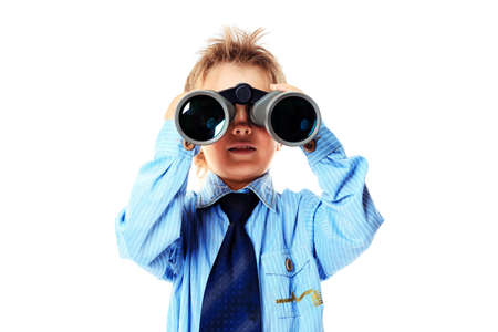 Curious little boy is looking through binoculars. Isolated over white background. photo