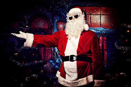 nicholas: Santa Claus is listening to music in headphones. Christmas. Stock Photo