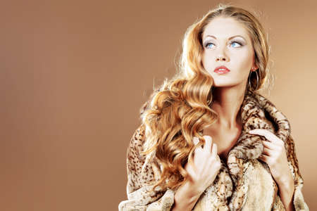 Beautiful glamorous woman in fur coat posing at studio. photo
