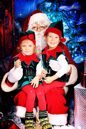snow man party: Santa Claus sitting with two little cute elves over Christmas background.