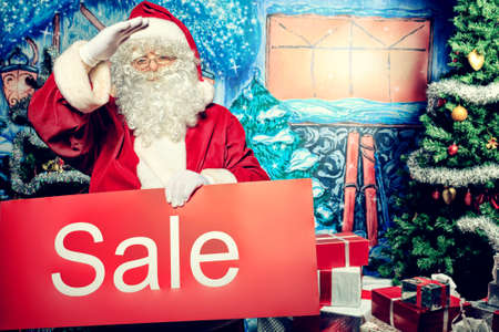 nick: Santa Claus holding sale board over Christmas background.