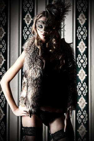 Gorgeous young woman in mask wearing sexual lingerie. Vintage background. photo