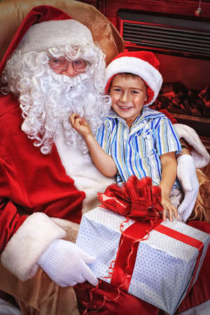 Santa Claus giving a present to a little cute boy at home. Stock Photo - 16105571