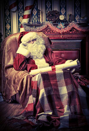 nick: Santa Claus with a list of Christmas presents sitting in a comfortable chair near the fireplace at home.