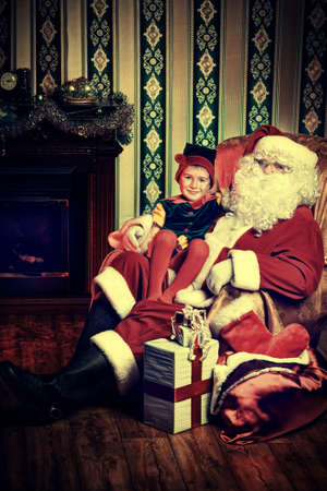 Santa Claus sitting with a little cute boy elf near the fireplace at home. Stock Photo - 16105627