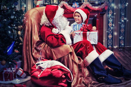 Santa Claus giving a present to a little cute boy near the fireplace and Christmas tree at home. Stock Photo