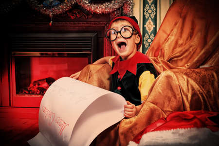 christmas costume: Little cute elf boy is reading a letter to Santa Claus at home. Stock Photo