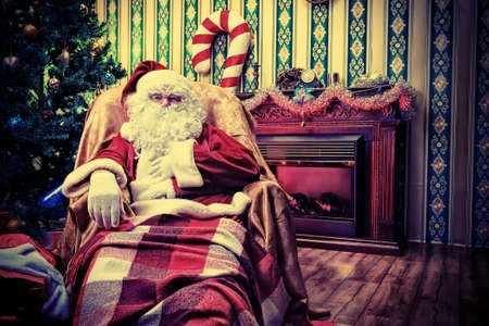 Santa Claus having a rest in a comfortable chair near the fireplace at home. Stock Photo - 16105573