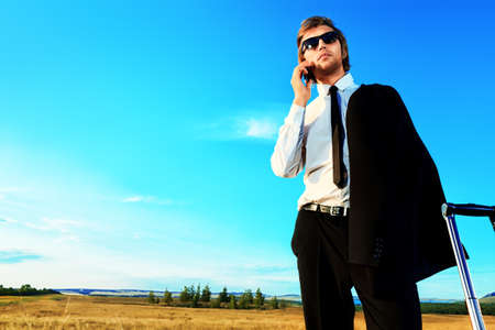 businessman waiting call: Handsome business man standing on a highway with his suitcase and calling by phone.