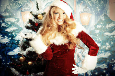 snow maiden: Beautiful young woman in Santa Claus clothes over Christmas background.