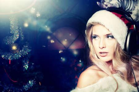 Joven y bella mujer en ropa de Santa Claus y auriculares sobre fondo de Navidad. Foto de archivo