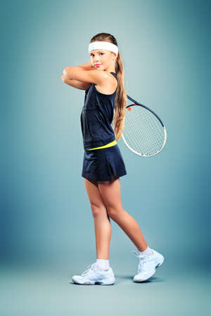 Portrait of a girl tennis player holding tennis racket  Studio shot