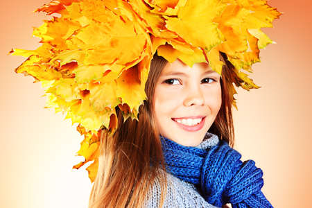 Portrait of a smiling girl in autumn clothes and a hat of maple leaves Stock Photo - 16165361