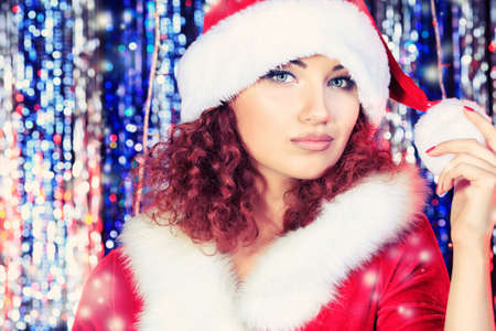 Attractive young woman in Christmas clothes on a party  Disco lights in the background  photo