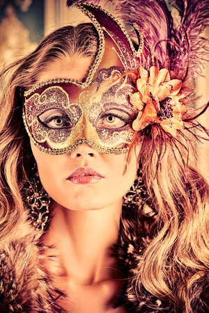 masked woman: Beautiful young woman in a carnival mask over vintage background.  Stock Photo