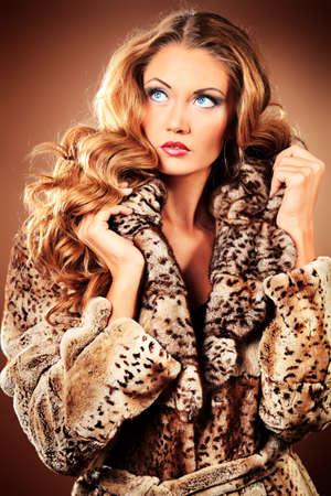 bontjas: Mooie glamoureuze vrouw in bontjas poseren in de studio. Stockfoto