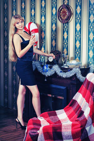 Beautiful young woman celebrating Christmas near the fireplace at home. photo