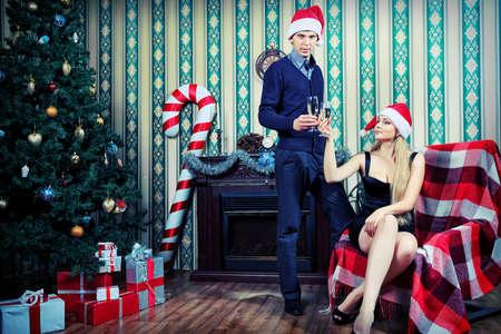 camino natale: Happy giovane coppia festeggiare il Natale vicino all'albero di Natale e camino a casa. Archivio Fotografico