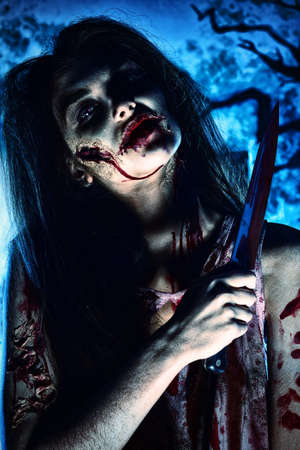 Bloodthirsty zombi with a knife standing at the night cemetery in the mist and moonlight. photo