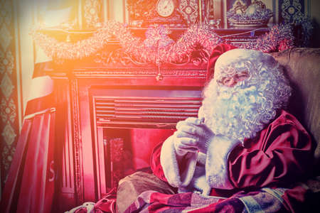 Santa Claus having a rest in a comfortable chair near the fireplace at home.  photo