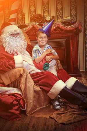 Santa Claus giving a present to a little cute boy at home. Stock Photo - 16216162