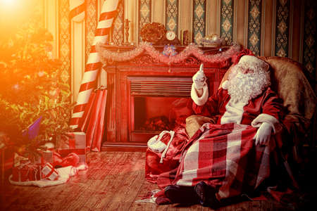 Santa Claus having a rest in a comfortable chair near the fireplace at home. Stock Photo - 16216164