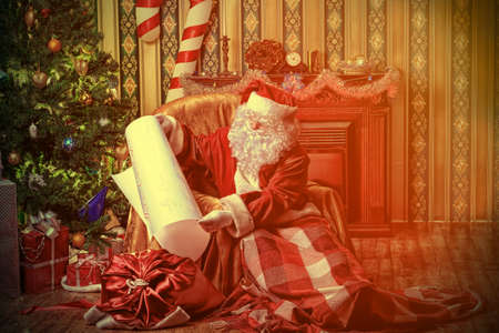Santa Claus with a list of Christmas presents sitting in a comfortable chair near the fireplace at home.  Stock Photo - 16216163