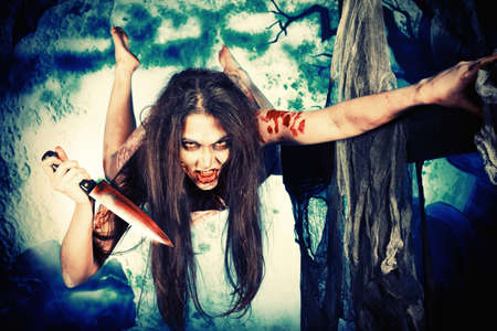 woman knife: Bloodthirsty zombi with a knife at the night cemetery in the mist and moonlight.