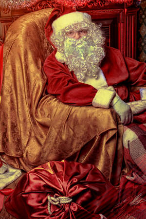 nicholas: Santa Claus having a rest in a comfortable chair near the fireplace at home.